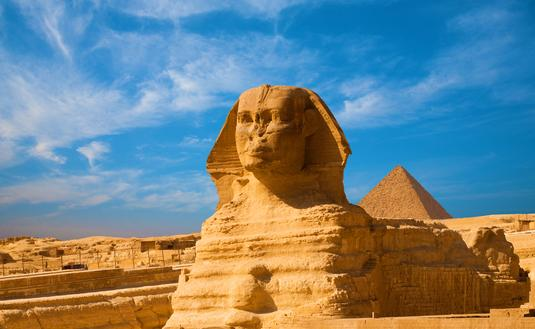 Full length body profile of Great Sphinx including head, feet with great pyramid of Menkaure in background on a clear, blue sky day in Giza, Egypt empty with no people. (photo via pius99 / iStock / Getty Images Plus)