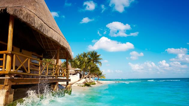 Playa del Carmen beach palapa in Riviera Maya Caribbean at Mayan Mexico (photo via LUNAMARINA / iStock / Getty Images Plus)