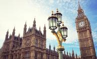 Big Ben in London with the houses of parliament and ornate street lamp (photo via BrianAJackson / iStock / Getty Images Plus)