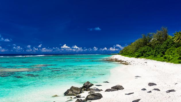 Amazing beach with white sand and black rocks on Rarotonga, Cook Islands (Photo via mvaligursky / iStock / Getty Images Plus)