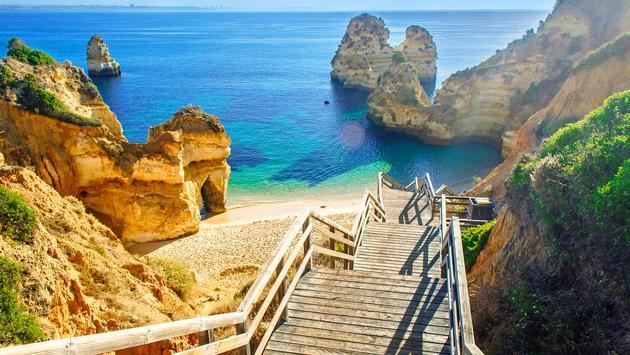 Wooden footbridge to beautiful beach Praia do Camilo near Lagos in algarve region, Portugal (Photo via samael334 / iStock / Getty Images Plus)