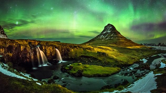 Aurora borealis at Mount Kirkjufell Iceland (photo via SuppalakKlabdee / iStock / Getty Images Plus)