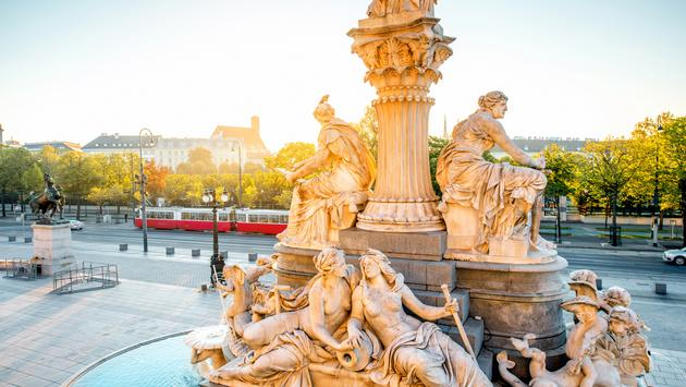 Athena statue near Parlament building with Vienna cityscape and old tram on the background on the sunrise (photo via RossHelen / iStock / Getty Images Plus)