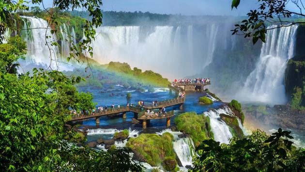Tourists at Iguazu Falls, Foz do Iguacu, Brazil.  (photo via rmnunes/iStock/Getty Images Plus)