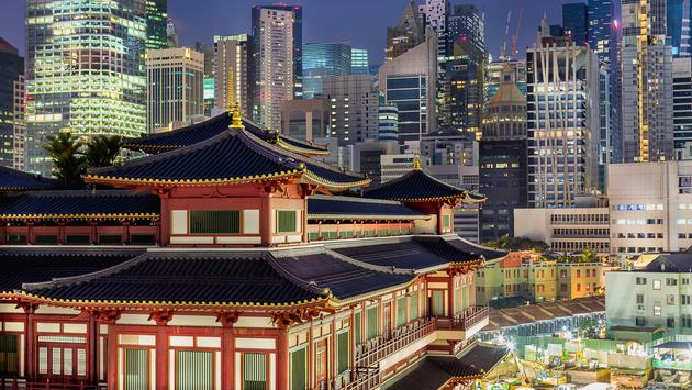 The famous Buddha Tooth Relic Temple in China town, Singapore. A stunning Chinese-style architecture among tall buildings with city lights. (photo via Prangthip_K / iStock / Getty Images Plus)