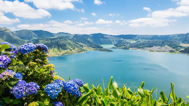 Lake of Sete Cidades with hortensia's, Azores, Portugal Europe (photo via VickySP / iStock / Getty Images Plus)