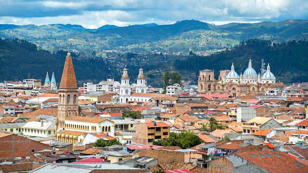 View of the city of Cuenca, Ecuador, with it's many churches and rooftops, on a cloudy day (photo via AlanFalcony / iStock / Getty Images Plus)