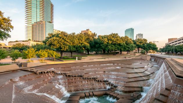 The Fort Worth, Texas water gardens in downtown Fort Worth. Concrete design with multiple waterfalls and water features. Trees fill the background, along with tall city buildings. A sunny summer day in an urban park. (photo via mchattenphotography / iStoc