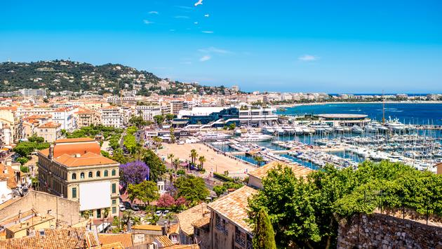 Top cityscape view on french riviera with yachts in Cannes city (Photo via  RossHelen / iStock / Getty Images Plus)