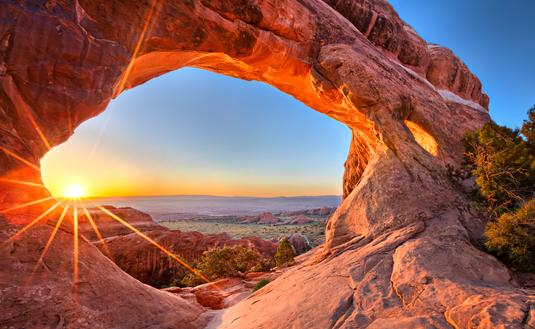 Sunrise at Partition Arch, in Arches National Park. (photo via tonda / iStock / Getty Images Plus)