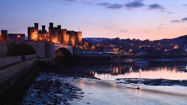 Conwy castle at dusk in north Wales UK (photo via olliemtdog / iStock / Getty Images Plus)