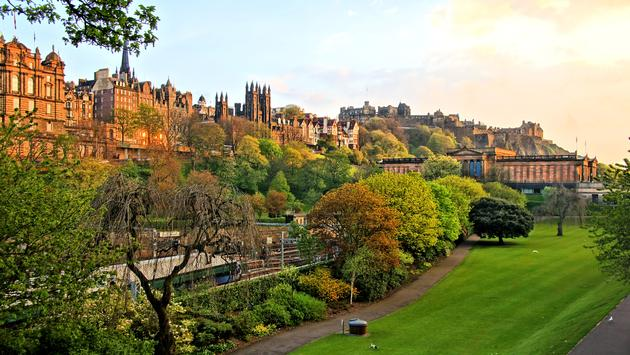 View of old Edinburgh, Scotland at sunset from Princes Street Gardens (photo via jenifoto / iStock / Getty Images Plus)