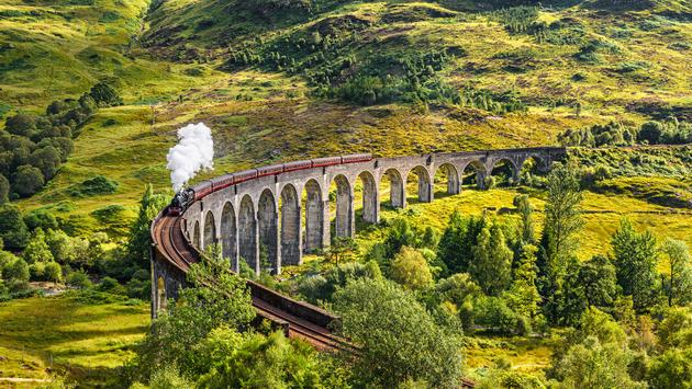 Glenfinnan Railway Viaduct in Scotland with the Jacobite steam train passing over (photo via miroslav_1 / iStock / Getty Images Plus(
