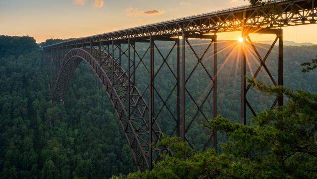 Setting sun behind the girders of the high arched New River Gorge bridge in West Virginia (photo via BackyardProduction / iStock / Getty Images Plus)