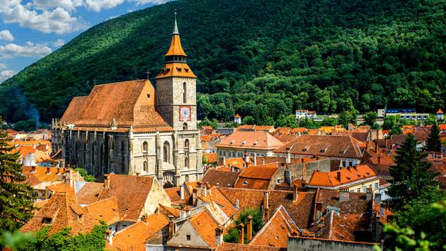 Brasov cityscape with black cathedral and mountain on backround in Romania (photo via RossHelen / iStock / Getty Images Plus)