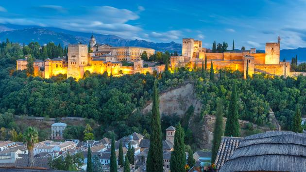 Palace of Charles V and roofs of Albayzin during evening blue hour in Granada, Andalusia, Spain (photo via KavalenkavaVolha/iStock/Getty Images Plus)