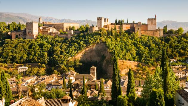 View of Granada in Andalucia, Spain, with the famous Alhambra on the hill in the distance (photo via IvanBastien/iStock/Getty Images Plus)
