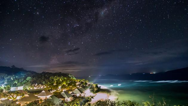 Magnific milky way over the bungalows in the pacific island of Tokoriki, Fiji. (photo via Rune_Landale / iStock / Getty Images Plus)
