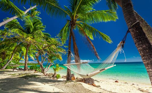 Empty hammock in the shade of palm trees on tropical Fiji Islands (photo via mvaligursky / iStock / Getty Images Plus)