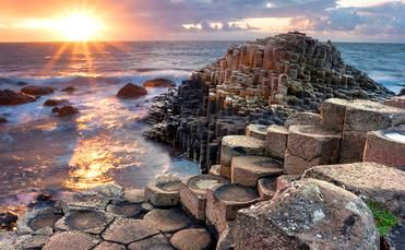 People visiting Giant s Causeway at the sunset in North Antrim, Northern Ireland (Aitormmfoto / iStock / Getty Images Plus)