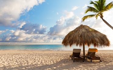 Beach chairs with umbrella and beautiful sand beach in Punta Cana, Dominican Republic (Photo via Preto_perola / iStock / Getty Images Plus)