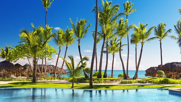 Tropical beach resort with umbrellas and lounge chairs in Punta Cana, Dominican Republic (Photo via Preto_perola / iStock / Getty Images Plus)