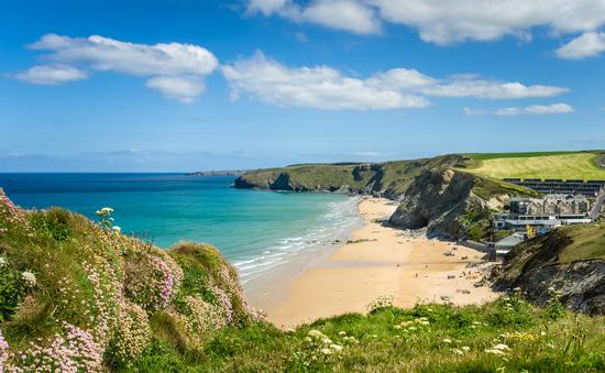 Photo of a Stretch of Coast in Cornwall with a Sandy Beach at the foot of high cliffs. (Photo via AlbertPego / iStock / Getty Images Plus)