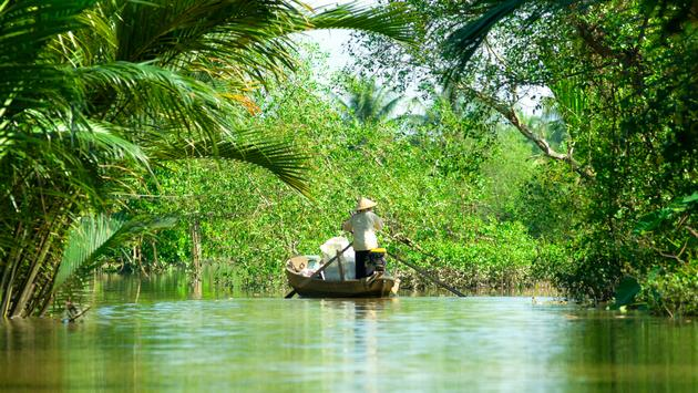 Woman driving a boat in the mekong delta. Vietnam. (photo via MasterLu / iStock / Getty Images Plus)