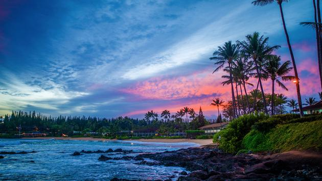 a glowing pink sunrise over the rocky lava and sandy beach, of napili bay, maui, hawaii (photo via StevenGaertner / iStock / Getty Images Plus)