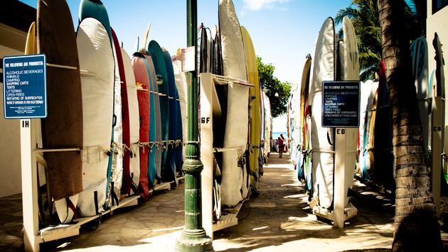 Colorful hawaiian surf boards parking rack in waikiki (photo via mdlart / iStock / Getty Images Plus)
