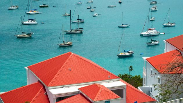 Red roof tops overlooking the brilliant turquoise blue Caribbean bay with boats in downtown St. Croix, US Virgin Islands. (photo via JulieHewitt / iStock / Getty Images Plus)