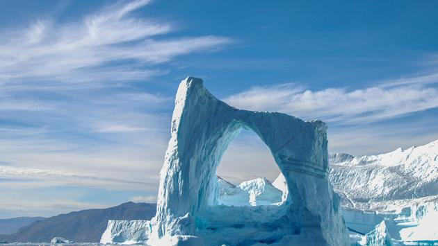 A beautiful arch iceberg in Greenland (photo via HenriVdl/iStock/Getty Images Plus)