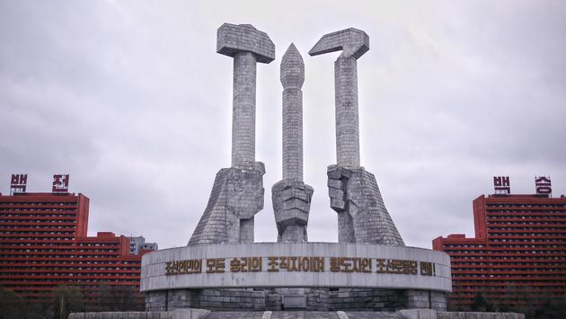 """The iconic North Korea Worker's Party Monument in Pyongyang, DPRK, represents the three pillars of the Revolution: Workers (hammer), Farmers (sickle), and Intellectuals (brush). The slogan says: """"The organizers of the victory of the Korean people and the"""