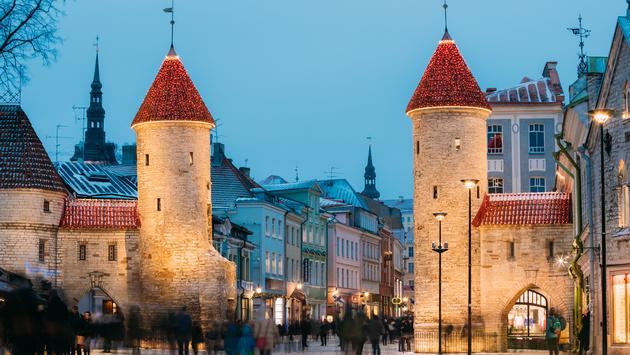 Tallinn, Estonia. Famous Landmark Viru Gate In Street Lighting At Evening Or Night Illumination. Christmas, Xmas, New Year Holiday Vacation In Old Town. Popular Touristic Place (photo via bruev / iStock / Getty Images Plus)