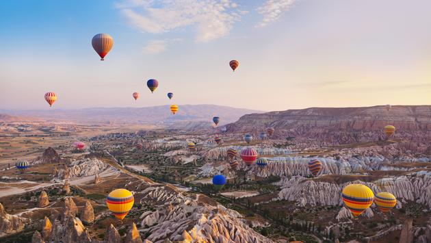 Hot air balloon flying over rock landscape at Cappadocia Turkey (photo via TPopova / iStock / Getty Images Plus)