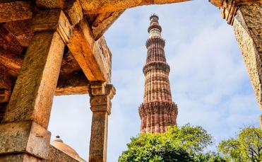 Qutub Minar Tower, Delhi India (photo via DVrcan / iStock / Getty Images Plus)