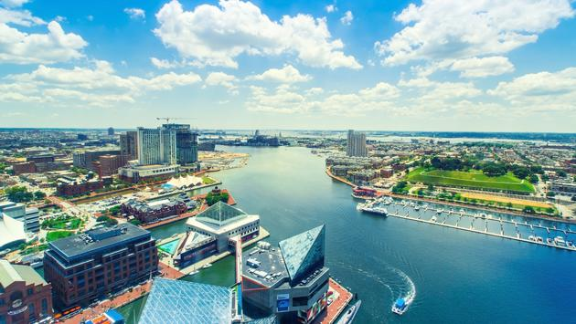 Aerial view of the Inner Harbor of Baltimore, Maryland on a clear summer day (photo via Melpomenem / iStock / Getty Images Plus)