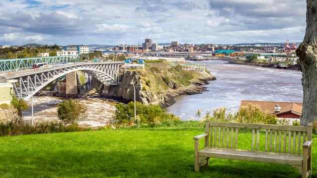 Photo of Saint John, New Brunswick, from a park near the Reversing Falls Bridge. An empty wooden bench is in Foreground. (photo via AlbertPego / iStock / Getty Images Plus)