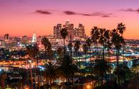 Beautiful sunset of Los Angeles downtown skyline and palm trees in foreground (Photo via choness / iStock / Getty Images Plus)