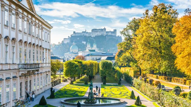 Beautiful view of famous Mirabell Gardens with the old historic Fortress Hohensalzburg in the background in Salzburg, Austria (photo via bluejayphoto / iStock / Getty Images Plus)