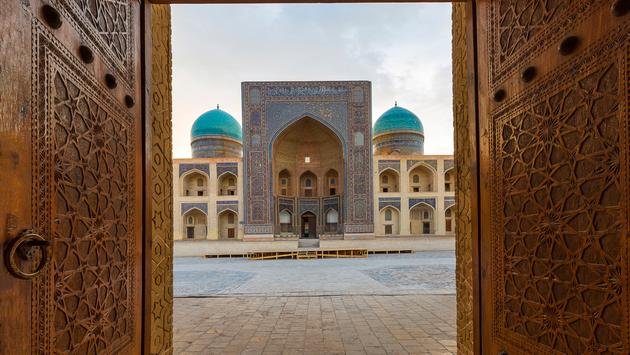 Blue domes of the Madressa through open wooden door in Bukhara, Uzbekistan. (photo via Ozbalci / iStock / Getty Images Plus)