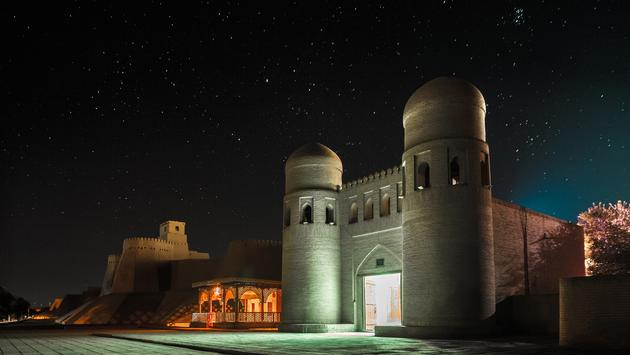 Western gate (Ata Darvoza) to ancient town of Itchan Kala at night with stars. Khiva, Uzbekistan (photo via mihtiander / iStock / Getty Images Plus)