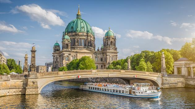 Berlin Cathedral with ship on Spree river at sunset, Berlin, Germany (Photo via bluejayphoto / iStock / Getty Images Plus)