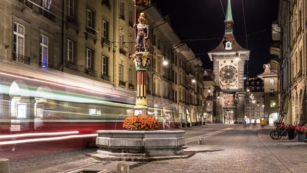 A tram rushes through the streets of Bern old town with the Zytgolgge tower in the background in Switzerland capital city at night. (Photo via AsianDream / iStock / Getty Images Plus)