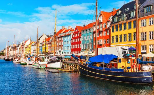 Scenic summer view of Nyhavn pier with color buildings, ships, yachts and other boats in the Old Town of Copenhagen, Denmark (Photo via scanrail / iStock / Getty Images Plus)