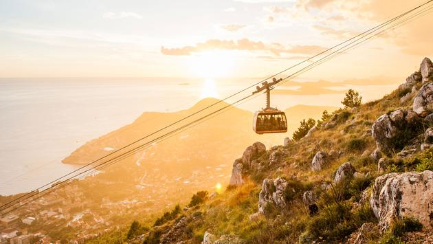 Photo of the cable car in Dubrovnik at sunset. (photo via Toni_Poikeljarvi / iStock / Getty Images Plus)