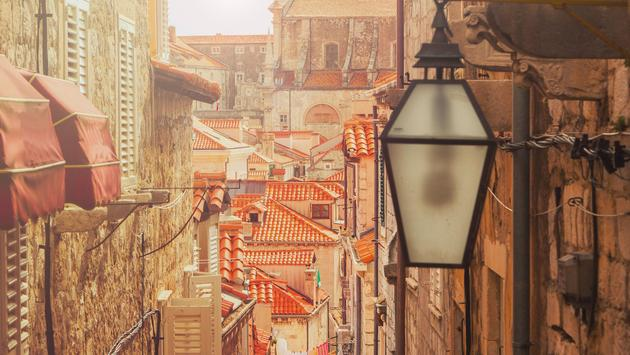 Dubrovnik old city street view in Croatia, warm filter, lens flare (photo via iascic / iStock / Getty Images Plus)
