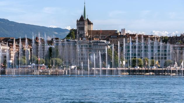 Fountain show at the Geneva Lake Festival in august. View from the lake on the Saint Piere Cathedral (photo via eugeniek/iStock/Getty Images Plus)