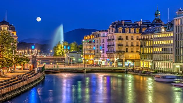 Urban view with famous fountain by night with full moon, Geneva, Switzerland (photo via Elenarts/iStock/Getty Images Plus)