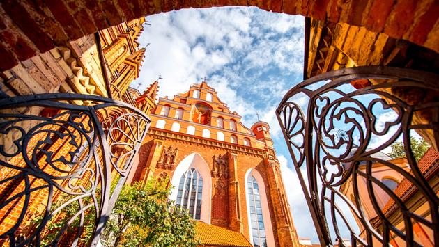 View from the gates on the beautiful Francis of Assisi gothic church in the old town of Vilnius city, Lithuania. (photo via RossHelen / iStock / Getty Images Plus)